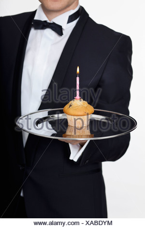 A butler presenting a muffin with a lit birthday candle on a silver tray, focus on hand - Stock Photo