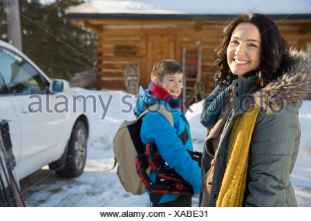Portrait of mother standing in front of winter cabin - Stock Photo