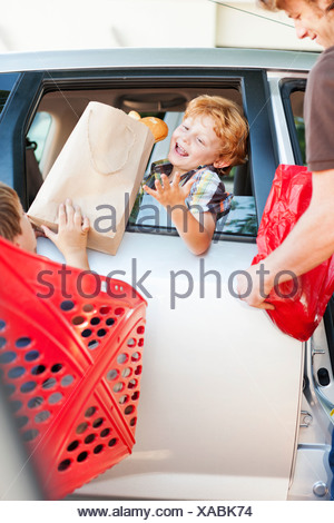 Father and sons loading groceries in car - Stock Photo