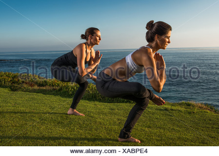 Women on cliff, in yoga positions - Stock Photo