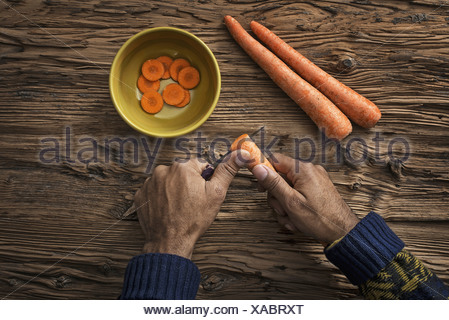 A person holding and slicing fresh carrots into a bowl - Stock Photo