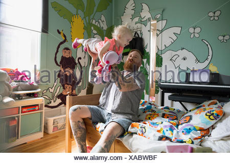 Playful father flying daughter in bedroom - Stock Photo