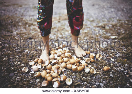 Low section shot of woman walking on eggshells - Stock Photo