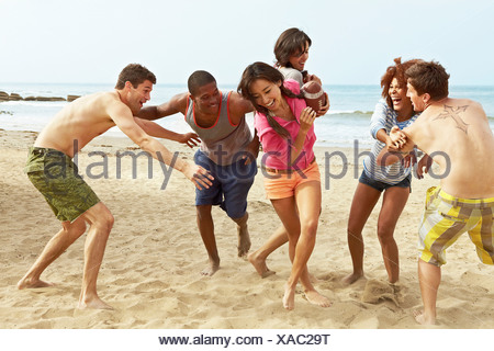 Friends on beach playing rugby - Stock Photo