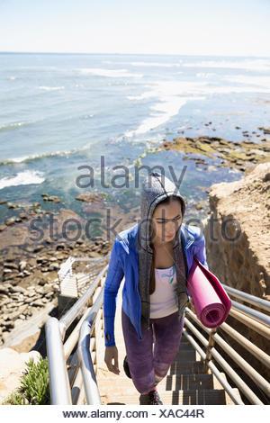 Latina woman with yoga mat climbing stairs above sunny ocean - Stock Photo