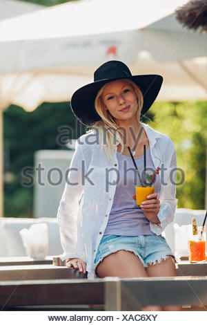 Portrait of young woman wearing hat sitting in an outdoor cafe with glass of orange juice - Stock Photo
