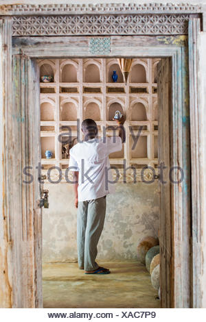 LAMU, KENYA, AFRICA. A man in white cotton shirt places art on a shelf in a historic courtyard. - Stock Photo
