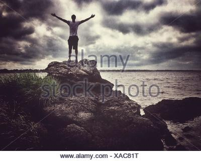 Man With Arms Outstretched Standing On Rocks Against Clouds Sky - Stock Photo