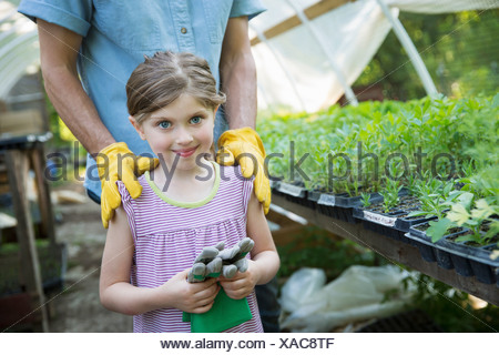 On farm Children adults working together man young child gardening gloves standing beside bench of young seedling plants in - Stock Photo