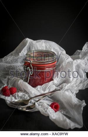 Jar of raw raspberry & chia jam in white paper before dark background - Stock Photo