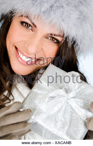 A young woman holding a Christmas present - Stock Photo