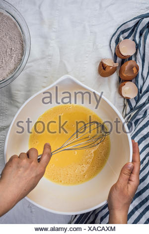 A woman whisking eggs in  large bowl photographed from top view. Egg shells accompany on the side. - Stock Photo