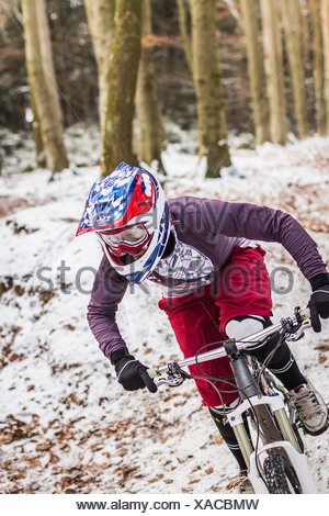 Young female mountain biker riding downhill through forest - Stock Photo