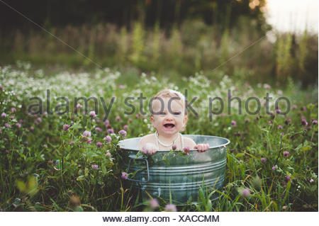 Baby girl bathing in a tin bathtub in a wild flower meadow - Stock Photo