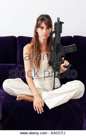 Woman holding machine gun on sofa - Stock Photo