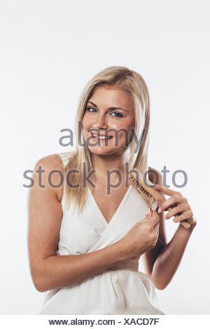 Woman brushing her hair - Stock Photo