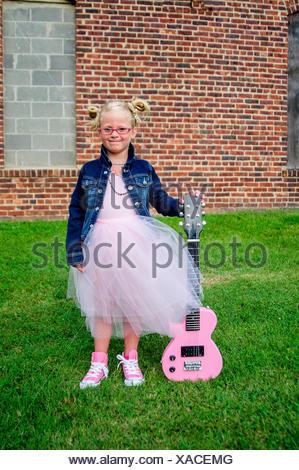 Young girl wearing tutu and denim jacket, holding guitar - Stock Photo