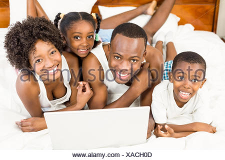 Happy family lying on the bed - Stock Photo