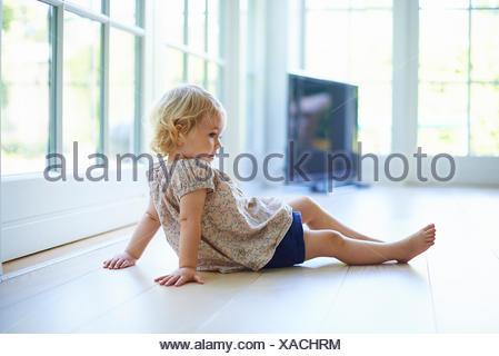 Portrait female toddler sitting on living room floor - Stock Photo