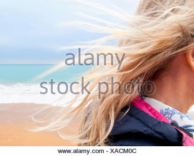 Blond hair blowing in breeze on beach - Stock Photo