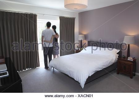 Couple looking through glass door - Stock Photo