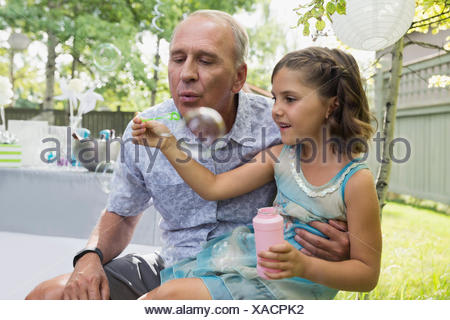 Grandfather and granddaughter blowing bubbles in backyard - Stock Photo