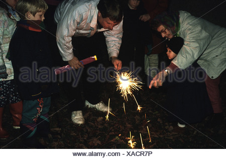 Family celebrating Guy Fawkes night lighting sparklers - Stock Photo