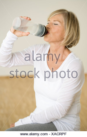 Senior woman drinking water, Munich, Bavaria, Germany - Stock Photo