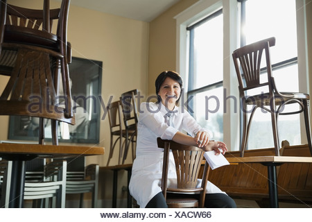 Portrait of smiling waitress sitting in cafe - Stock Photo