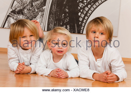 2 boys, 7 and 4 years, and a girl, 1.5 years, lying on the floor - Stock Photo