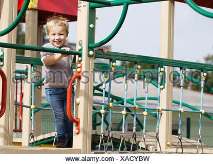 Boy on playground equipment. - Stock Photo