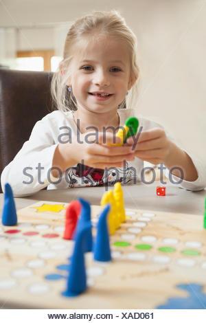 Girl playing board game, Bavaria, Germany - Stock Photo