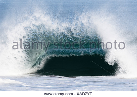 A large wave breaks with force over a shallow sandbar. - Stock Photo