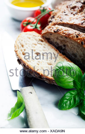Tomato, bread, basil and olive oil on white marble background. Italian cooking, healthy food or vegetarian concept - Stock Photo