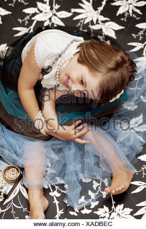 Portrait of a young girl playing dress up with costume jewelry - Stock Photo