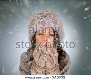 A young woman blowing snowflakes - Stock Photo
