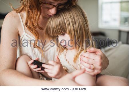 Mother hugging daughter, using smartphone - Stock Photo