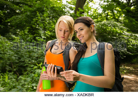 Women out walking in forest, looking at GPS - Stock Photo