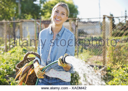 Portrait of woman watering plants with garden hose - Stock Photo