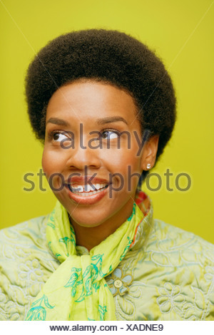 Close-up of a young woman smiling and looking sideways - Stock Photo