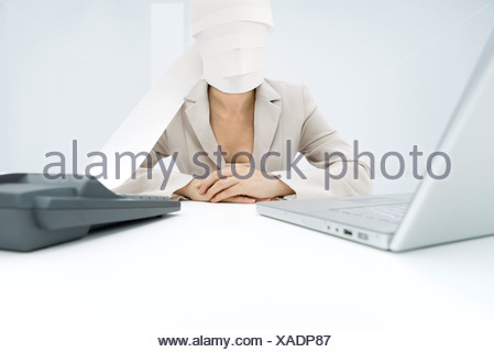 Professional woman sitting at desk, paper from adding machine wrapped around face - Stock Photo