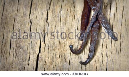 Bourbon vanilla beans isolated on wooden background. - Stock Photo