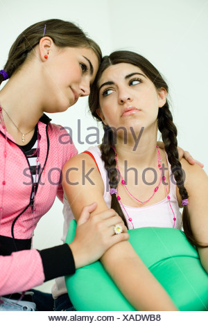 Two young female friends, one consoling the other - Stock Photo