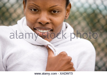 Woman wearing white hooded sports top smiling front view close up portrait - Stock Photo