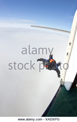 Mid adult man mid air preparing to fly in wingsuit - Stock Photo