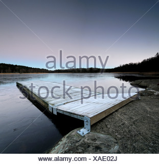 View of frost covered pier on lake - Stock Photo