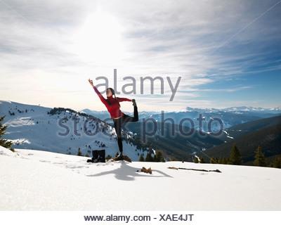 Young woman doing yoga pose on rock in snow in mountainous terrain - Stock Photo