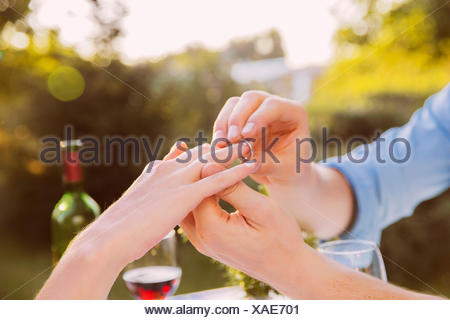 Man putting ring on woman's finger at dinner - Stock Photo