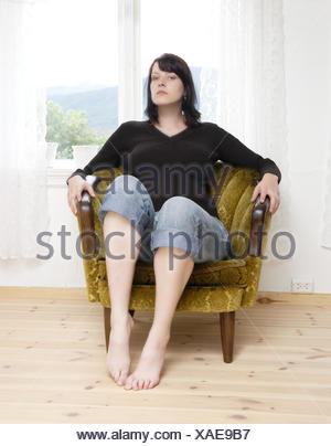 woman earnest armchair sour put sitting sit arrogance arrogant livingroom - Stock Photo