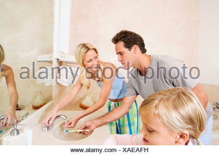 Couple rinsing off their toothbrushes under the faucet - Stock Photo